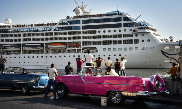 Cubans watch as the first US-to-Cuba cruise ship to arrive in the island nation in decades glides into the port of Havana, on May 2, 2016. The first US cruise ship bound for Cuba in half a century, the Adonia – a vessel from the Carnival cruise's Fathom line – set sail from Florida on Sunday, marking a new milestone in the rapprochement between Washington and Havana. The ship – with 700 passengers aboard – departed from Miami, the heart of the Cuban diaspora in the United States. (Photo by Adalberto Roque/AFP Photo)