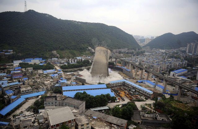 A cooling tower of a coal-burning power plant topples during a controlled demolition in Guiyang, Guizhou province, China, July 23, 2015. (Photo by Reuters/Stringer)