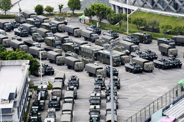 This Friday, August 16, 2019, photo shows armored vehicles and troop trucks are parked outside Shenzhen Bay Stadium in Shenzhen, China. Members of China's paramilitary People's Armed Police marched and practiced crowd control tactics at a sports complex in Shenzhen across from Hong Kong on Friday, in what some interpreted as a threat against pro-democracy protesters in the semiautonomous territory. (Photo by Madoka Ikegami/Kyodo News via AP Photo)