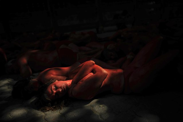 A woman with her body painted red,  protests against bull runs beside the bull ring a few days ahead to beginning the famous San Fermin Fiestas,  in Pamplona northern Spain, Saturday, July 4, 2015. (Photo by Alvaro Barrientos/AP Photo)