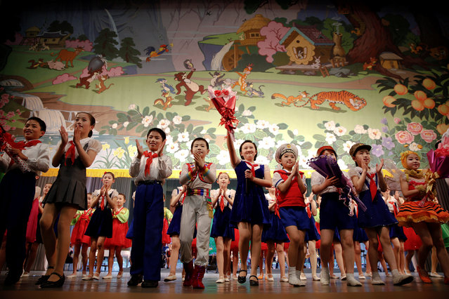 Children wave to spectators as the curtain is brought down at the end of a performance at the Mangyongdae Children's Palace in Pyongyang, North Korea May 5, 2016. (Photo by Damir Sagolj/Reuters)