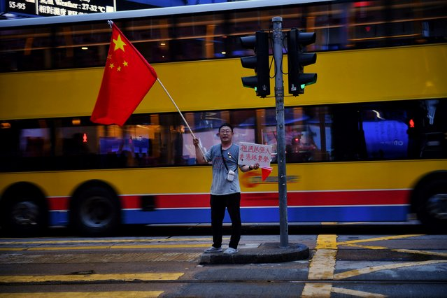 A lone pro-government supporter waves a China flag near Central in Hong Kong on August 26, 2019. (Photo by Lillian Suwanrumpha/AFP Photo)