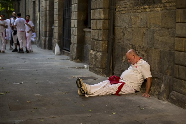 A reveler sleeps at a square during opening of the 2015 San Fermin fiestas in Pamplona, Spain, Monday, July 6, 2015. (Photo by Andres Kudacki/AP Photo)