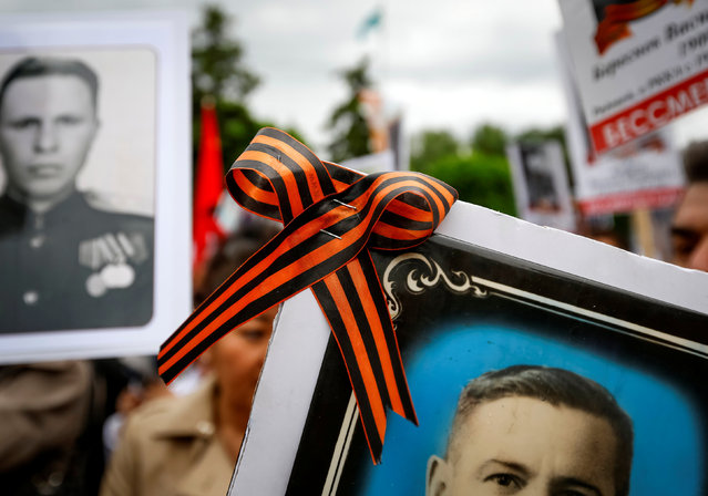 The black and orange ribbon of St. George is attached to a pictures as people carrying portraits of deceased relatives who took part in World War Two march in a parade during Victory Day commemorations in  Almaty, Kazakhstan, May 9, 2016. (Photo by Shamil Zhumatov/Reuters)