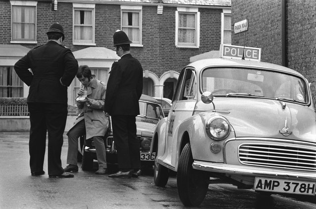 Two police officers administer a Breathalyser test to a driver on Finden Road in Newham, in the East End of London, 1960s. (Photo by Steve Lewis/Getty Images)