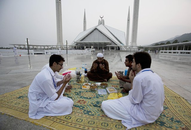Pakistani Muslims pray before breaking their fast during the holy month of Ramadan at Faisal mosque in Islamabad, Pakistan, Wednesday, July 8, 2015. Muslims across the world are observing the holy fasting month of Ramadan, where they refrain from eating, drinking and smoking from dawn to dusk. (Photo by B. K. Bangash/AP Photo)