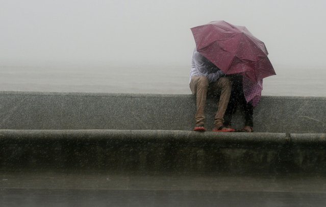 An Indian couple sit together under an umbrella during heavy rain showers at the sea front in Mumbai on July 12, 2013. The monsoon season, which runs from June to September, accounts for about 80 percent of India's annual rainfall, vital for a farm economy which lacks adequate irrigation facilities. (Photo by Punit Paranjpe/AFP Photo)