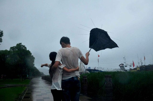 A couple make their way through a storm brought by typhoon Chan-hom in Ningbo, east China's Zhejiang province on July 11, 2015. Typhoon Chan-hom barrelled towards China's heavily populated eastern coast on July 11, forcing the evacuation of almost a million people, shutting transport links and devastating swathes of farmland, the government and state media said. (Photo by AFP Photo)