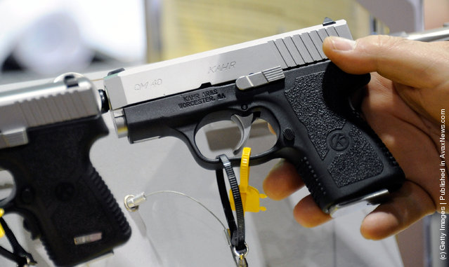 An attendee holds a Kahr Arms CM40 pistol at the company's booth