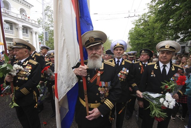 Former Soviet servicemen march with a Soviet navy flag to mark Victory Day in the Crimean port of Sevastopol May 9, 2014. (Photo by Reuters/Stringer)