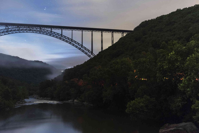 In this Wednesday, June 19, 2019 photo taken with a slow shutter speed, thousands of lightning bugs light up the trees along the New River Gorge as the New River Gorge bridge towers above as seen from the Fayette Station Road bridge in Fayetteville, W.Va. (Photo by Craig Hudson/Charleston Gazette-Mail via AP Photo)