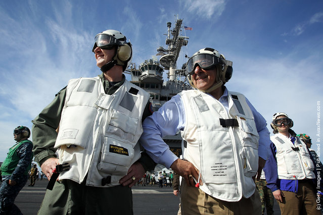 U.S. Secretary of Defense Leon E. Panetta (R), escorted by Commander of Strike Group Twelve Rear Admiral Walter E. Carter, Jr. (L), watches day flight operations from the flight deck of the aircraft carrier USS Enterprise