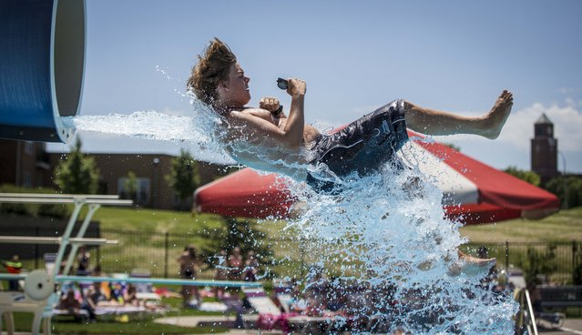 Clive Aquatic Center lifeguard Sam Cohrs exits the water slide for a pool check as temperatures rise Monday, July 13, 2015, in Clive, Iowa. The National Weather Service has issued an excessive heat warning for parts of Kansas, Missouri, Iowa and Illinois. (Photo by Rodney White/The Des Moines Register via AP Photo)