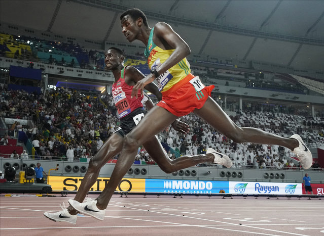 Conseslus Kipruto, left, of Kenya, wins ahead of Lamecha Girma, right, of Ethiopia, in the men's 3000 meter steeplechase final at the World Athletics Championships in Doha, Qatar, Friday, October 4, 2019. (Photo by David J. Phillip/AP Photo)