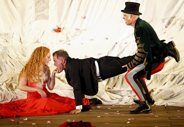 """Actors Cornelius Obonya as Jedermann (C), Stephan Kreiss as Duenner Vetter (R) and actress Brigitte Hobmeier as Buhlschaft perform on stage during a dress rehearsal of Hugo von Hofmannsthal's drama """"Jedermann"""" (Everyman) at Domplatz square in Salzburg, Austria, July 16, 2015. The play is directed by Julian Crouch and Brian Mertes and will premiere as part of the annual Salzburg cultural Festival on July 19, 2015. (Photo by Leonhard Foeger/Reuters)"""