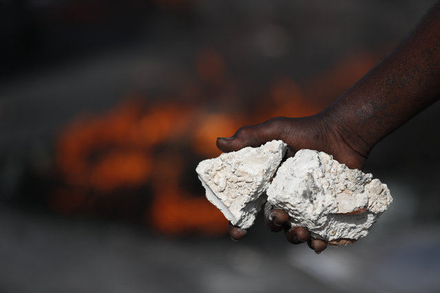 A protestor holds rocks while walking in front of burning tires at a barricade, as protesters seek to paralyze transport and commerce in order to pressure President Jovenel Moise to resign, in Port-au-Prince, Haiti, Tuesday, October 8, 2019. The U.N.'s Mission for Justice Support in Haiti has urged the government to ensure the normal functioning of schools, hospitals and emergency services and allow aid to reach the most vulnerable people. (Photo by Rebecca Blackwell/AP Photo)