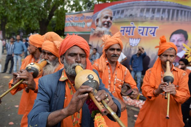 """A band of Indian musicians plays music for a group of paying customers who wanted to dance as they celebrate at the Bharatiya Janata Party (BJP) headquarters in New Delhi on May 16, 2014. India's triumphant Hindu nationalists declared """"the start of a new era"""" in the world's biggest democracy after hardline BJP leader Narendra Modi propelled them to a stunning win on a platform of revitalizing the sickly economy. (Photo by Roberto Schmidt/AFP Photo)"""