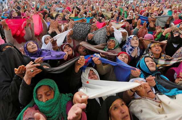 Kashmiri Muslim women pray upon seeing a relic believed to be hair from the beard of Prophet Mohammed during Meeraj-un-Nabi, a festival which marks the ascension of Prophet Mohammed to Heaven, at the Hazratbal shrine in Srinagar, April 25, 2017. (Photo by Danish Ismail/Reuters)