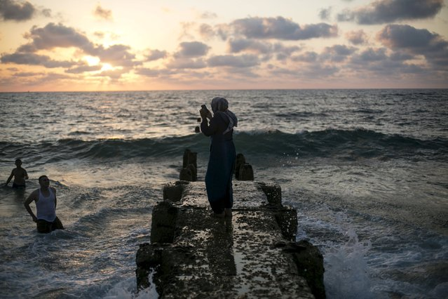 A Muslim woman takes a picture of a man in the water of the Mediterranean sea in Tel Aviv during Eid al-Fitr, which marks the end of the holy month of Ramadan July 19, 2015. (Photo by Baz Ratner/Reuters)