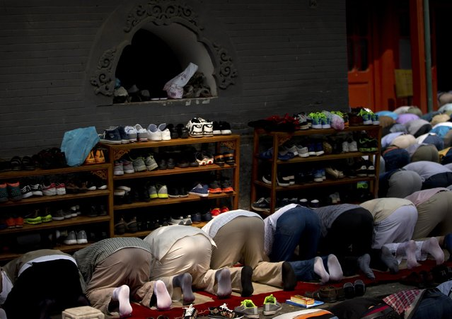 Liu Shoupeng, a Chinese Muslim and retired electrical engineer, third from left, prays with fellow worshipers during Eid al-Fitr prayers at Niujie Mosque, the oldest and largest mosque in Beijing, Saturday, July 18, 2015. Liu, 74, a member of the Muslim Hui minority group, is a devout believer who says he has not missed a day of prayer in 15 years and attends the same mosque that his father and grandfather did. (Photo by Mark Schiefelbein/AP Photo)