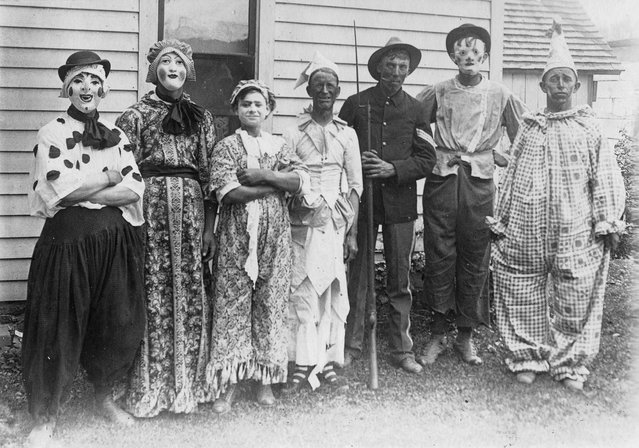 Postcard features a group of party goers in Halloween costumes, early twentieth century. (Photo by Transcendental Graphics/Getty Images)