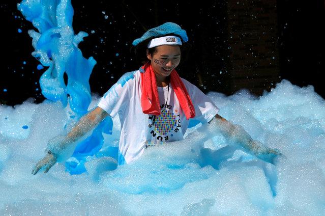 A participant runs through foam during the Love Foam Run race in Hsinchu, Taiwan May 29, 2016. (Photo by Tyrone Siu/Reuters)