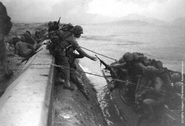 US Marines land from assault craft and climb over the sea defences at Inchon in South Korea during the Korean War, after heavy bombardment of coastal defences by warships