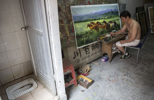 An artist works on a large canvas in his gallery at the artist village on June 12, 2014 in Shenzhen, China. The Dafen Artist Village in Guangdong province, China, is home to thousands of artists who reproduce some of the world's most iconic paintings as well as create their own works. The village, on the outskirts of Shenzhen, is becoming a major center for original Chinese art. (Photo by Palani Mohan/Getty images)