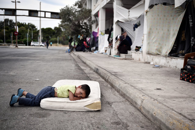 A refugee boy rests in the makeshift camp situated at the old Athens airport on June 13, 2016. (Photo by Louisa Gouliamaki/AFP Photo)