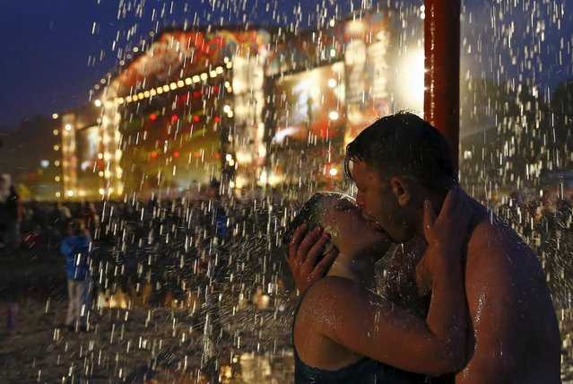A couple kiss as they shower in a mud pit near the main stage during the 21st Woodstock Festival in Kostrzyn-upon-Odra, Poland, July 31, 2015. An estimated 200,000 people attended the ongoing festival, a brainchild of Polish journalist and social campaigner Jerzy Owsiak, on Friday. Owsiak initiated the event to say thank you to those who donated money to his GOCC charity organisation that delivers medical care for children. (Photo by Kacper Pempel/Reuters)