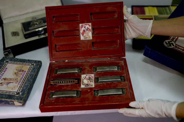A member of the federal police shows a box with swastikas containing harmonicas for children at the Interpol headquarters in Buenos Aires, Argentina, Friday, June 16, 2017. (Photo by Natacha Pisarenko/AP Photo)