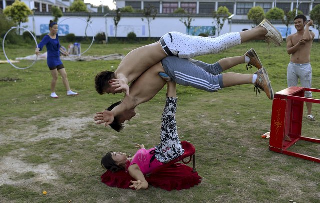A woman (bottom) balance two men with her feet as students practice at an acrobatic school in Sanwang village, Anhui province, China, July 30, 2015. Over 100 students, mostly young children are currently studying at the school. Most of them came from rural area of Henan, Shandong, Jiangsu and Anhui provinces. Starting at 4 a.m. every morning, students practice an average of 10 hours. The training usually lasts from one month to over a year. (Photo by Reuters/Stringer)