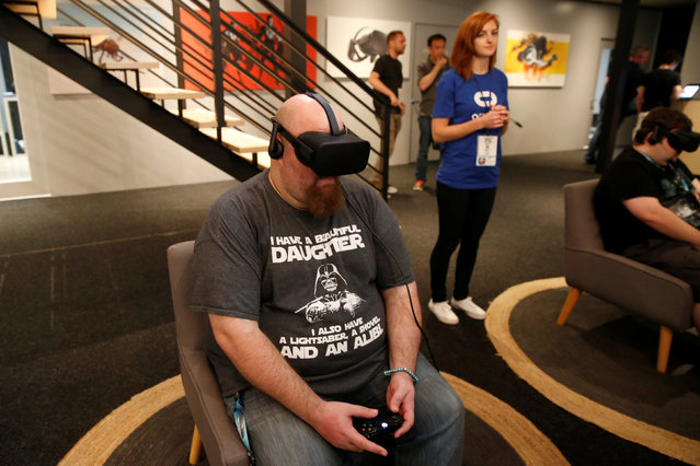 A man plays a video game with an Oculus Rift VR headset at the E3 Electronic Expo in Los Angeles, California, U.S. June 14, 2016. (Photo by Lucy Nicholson/Reuters)