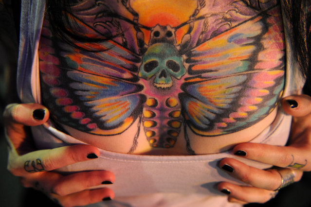 A woman shows off her tattoo during  during an International Congress of Tattoo Artists in Moscow, on May 18, 2012