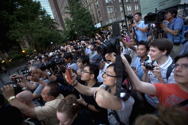 People crowd a bridge that goes over 42nd St as they take photos of the Manhattanhenge phenomenon in Manhattan borough of New York July 11, 2014. Manhattanhenge, coined by astrophysicist Neil deGrasse Tyson, occurs twice a year, when the setting sun aligns itself with the east-west grid of streets in Manhattan. (Photo by Carlo Allegri/Reuters)