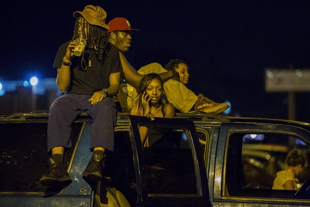 Onlookers watch as anti-police demonstrators march in protest in Ferguson, Missouri August 10, 2015. (Photo by Lucas Jackson/Reuters)