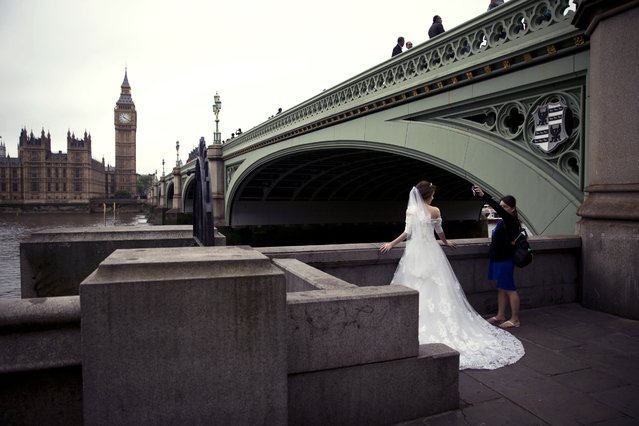 A woman assisting a photographer takes a light meter reading by the bride, during a photo shoot for a Malaysian couple after they got married, backdropped by the Houses of Parliament on the opposite side of the River Thames in London, Wednesday, June 22, 2016. Britain votes whether to stay in the European Union in a referendum on Thursday. (Photo by Matt Dunham/AP Photo)