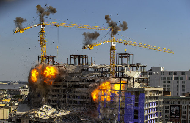 Two large cranes from the Hard Rock Hotel construction collapse come crashing down after being detonated for implosion in New Orleans, Sunday, October 20, 2019. Officials set off thundering explosions Sunday to topple two cranes looming precariously over a partially collapsed hotel in New Orleans, but most of one crane appeared to be left dangling atop the ruined building while the other crashed down. (Photo by David Grunfeld/The Advocate via AP Photo)