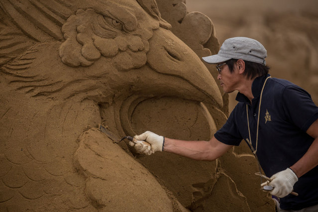 Sand sculptor Katsuhiko Chaen works on a large sand sculpture at the site of Yokohama Sand Art Exhibition – Culture City of East Asia 2014 on July 16, 2014 in Yokohama, Japan. Producer and sand sculptor Katsuhiko Chaen invited artists from around the world including South Korea and China, to recreate the World Heritage and historical buildings in China, Japan and South Korea. The exhibition will be open from July 19 to November 3, 2014. (Photo by Chris McGrath/Getty Images)