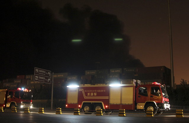 Firefighter's trucks are pictured in front of heavy smoke rising behind shipping containers after blasts at Binhai new district in Tianjin municipality, China, August 13, 2015. (Photo by Reuters/Stringer)