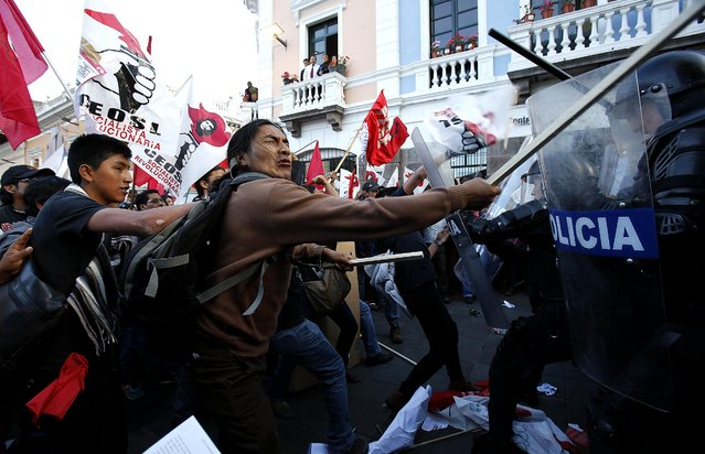 Protesting workers clash with police during a demonstration against changes to the national labor laws proposed by the government, in Quito, Ecuador, on Jule 17, 2014. The workers allege that reforms will negatively affect their right to strike and collective bargaining, as well as the end of the year pay bonuses for public and private employees. (Photo by Dolores Ochoa/Associated Press)