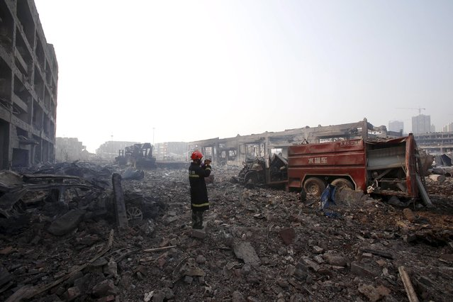 A firefighter films the aftermath next to a damaged firefighting vehicle at the site of Wednesday night's explosions in Binhai new district of Tianjin, China, August 15, 2015. (Photo by Reuters/China Daily)