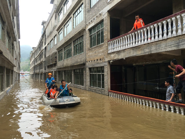 Rescuers row as they save residents with a boat at a flooded area in Zhijin, Guizhou Province, China, June 28, 2016. (Photo by Reuters/China Daily)