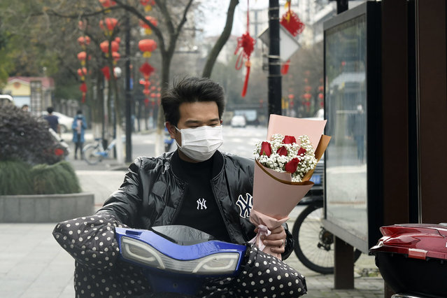 A man wearing a face mask carries a Valentine's Day bouquet as he rides a scooter in Hangzhou in eastern China's Zhejiang Province, Friday, February 14, 2020. China on Friday reported another sharp rise in the number of people infected with a new virus, as the death toll neared 1,400. (Photo by Chinatopix via AP Photo)