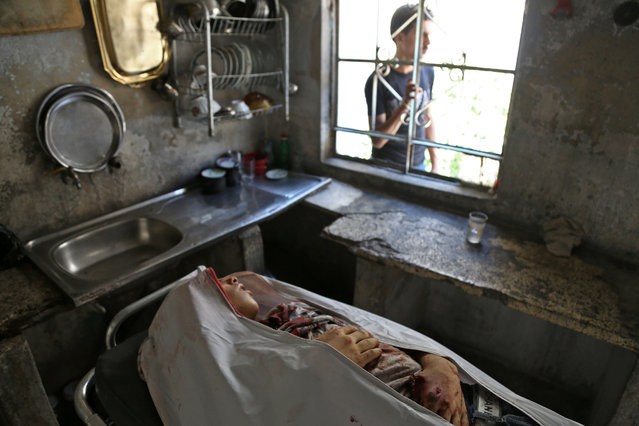 A picture taken on August 10, 2017 shows the body of a Syrian child who was reportedly killed during regime shellings in the rebel-controlled town of Hamouria, in the eastern Ghouta region on the outskirts of the capital Damascus, lying in his home kitchen prior to being prepared for funeral and burial. (Photo by Abdulmonam Eassa/AFP Photo)