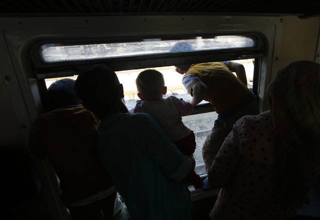 Migrants look out of a window onboard a crowded train taking them towards Serbia, at the railway station in the southern Macedonian town of Gevgelija, Wednesday, August 19, 2015. (Photo by Darko Vojinovic/AP Photo)