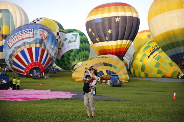 A woman takes a picture of a hot air balloon while her child rides in a sling during the 2016 International Hot Air Balloon Festival in Taitung, southeast of Taiwan, 01 July 2016. Thirty-one hot-air balloon teams from 14 countries join the six days of competition during the festival, which will run from 01 July to 07 August 2016. (Photo by Ritchie B. Tongo/EPA)
