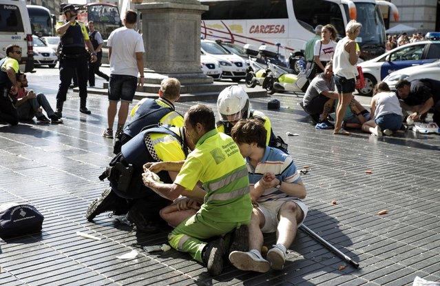 Medics and police tend to injured people near the scene of a terrorist attack in the Las Ramblas area on August 17, 2017 in Barcelona, Spain. Officials say 13 people are confirmed dead and at least 100 injured after a van plowed into people in the Las Ramblas area of the city this afternoon. (Photo by Nicolas Carvalho Ochoa/Getty Images)