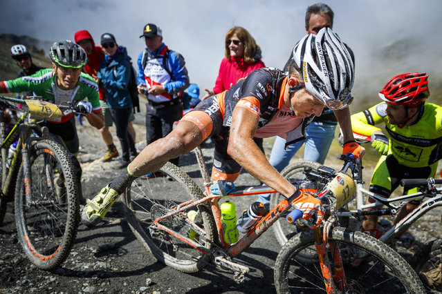"""Italian riders Juri Ragnoli, left, and Samuele Porro, right, push their bike on the """"Pas de Lona"""" to take respectively the second and first place of the 28th Swiss Mountain Bike Marathon """"Grand Raid"""" from Verbier to Grimentz, Southwestern Switzerland, Saturday, August 19, 2017. More than 2,000 mountain bikers took the start in different categories with the longest one stretching over 125 kilometers in length and 5025 meters of overall ascent. (Photo by Valentin Flauraud/Keystone via AP Photo)"""