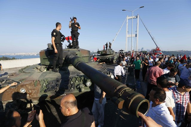 Policemen stand on a military vehicle after troops involved in the coup surrendered on the Bosphorus Bridge in Istanbul, Turkey July 16, 2016. (Photo by Murad Sezer/Reuters)
